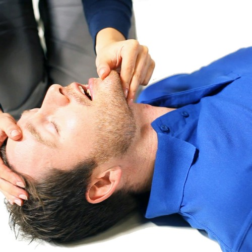 Adult performing first aid on a course
