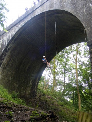 Adult abseiling off a bridge