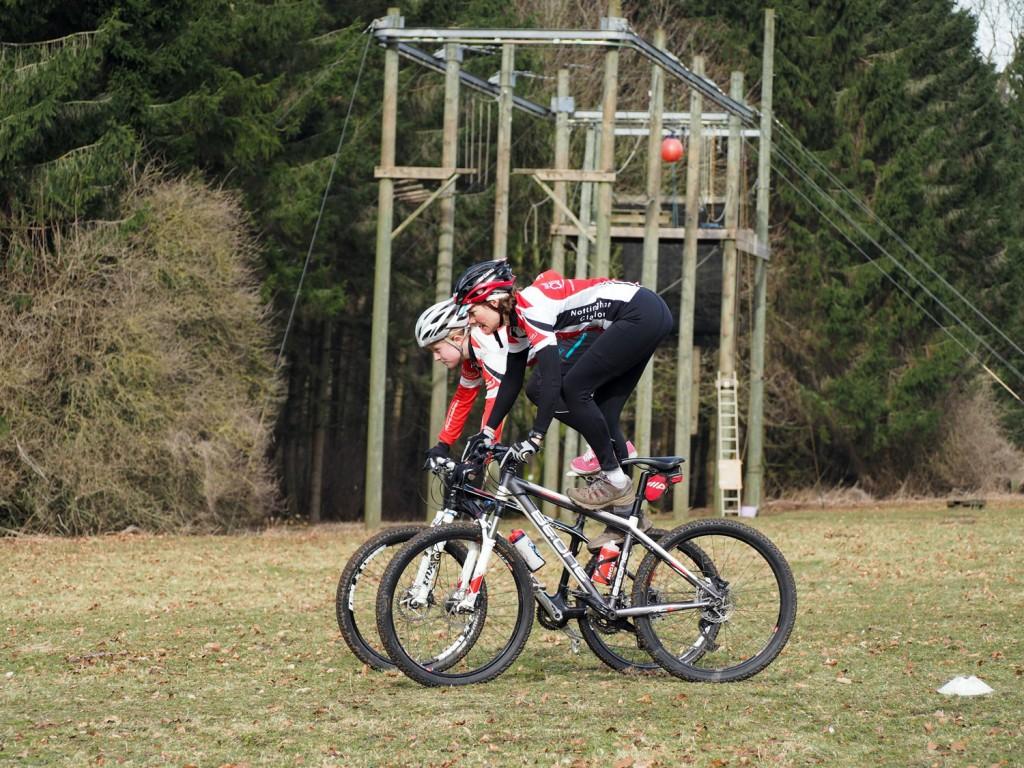 Two women performing skills on their mountain bikes