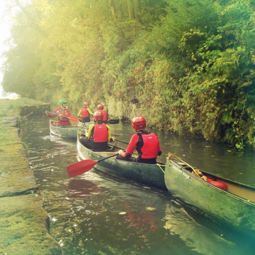 Pupils canoeing along a river