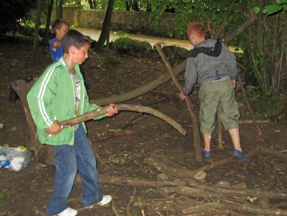 3 pupils building a den in the woods