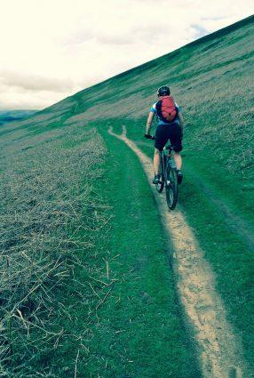 An adult riding a bike along a track