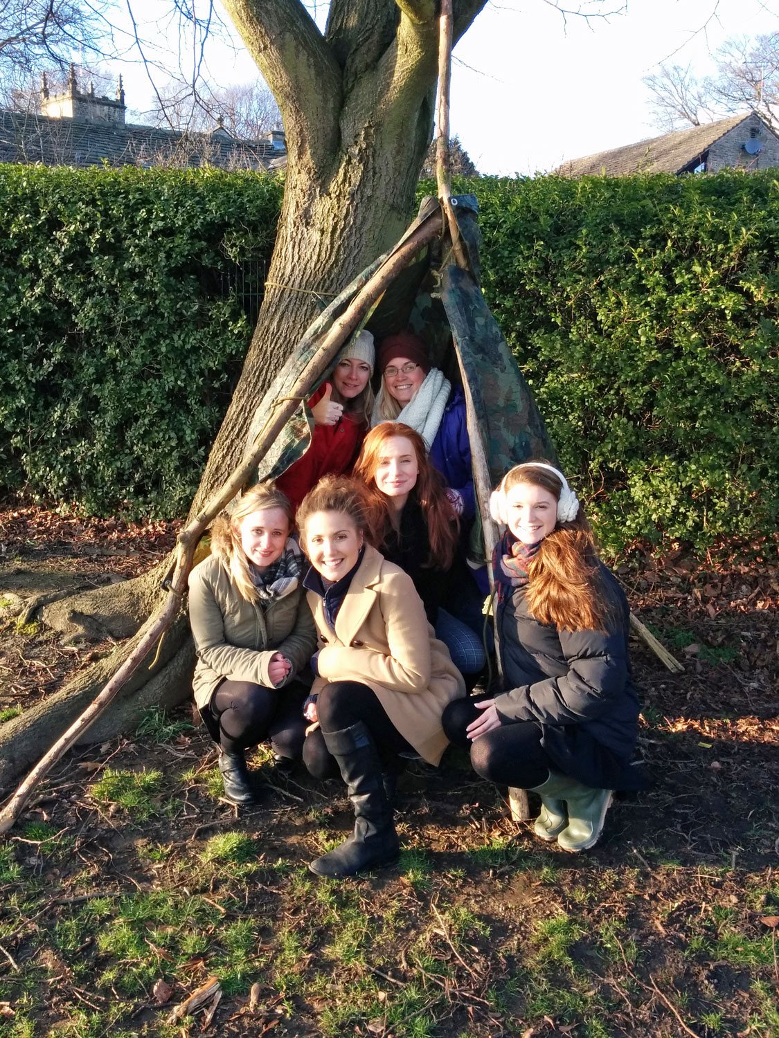 Teachers in a den made within the school grounds