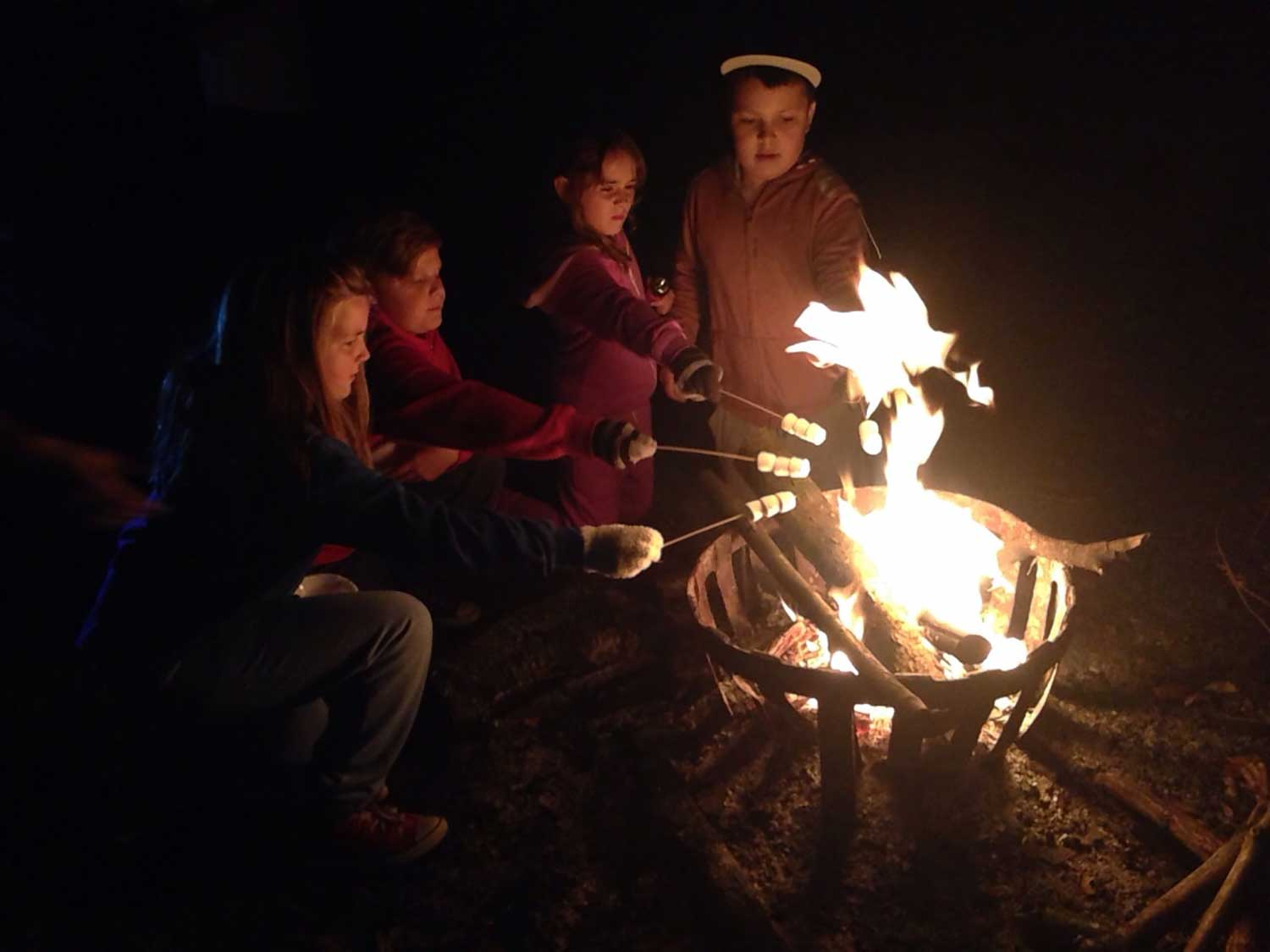 Pupils around a campfire (onsite ground-based) with marshmallows at Thornbridge Outdoors