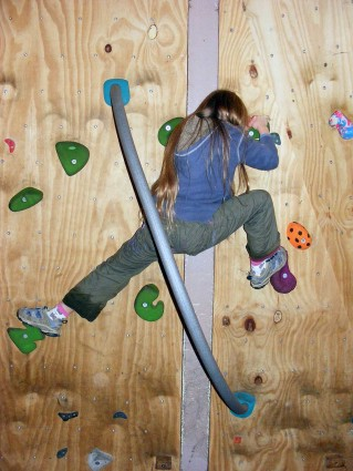 Pupil on the indoor bouldering wall (rock based activity) at Thornbridge Outdoors