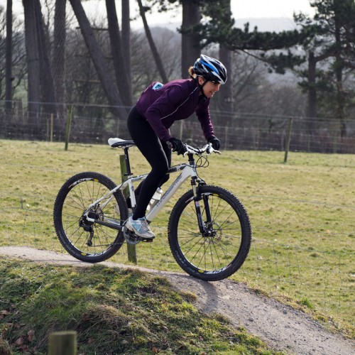 A women mountain biking on the bike trails and pump track at Thornbridge Outdoors