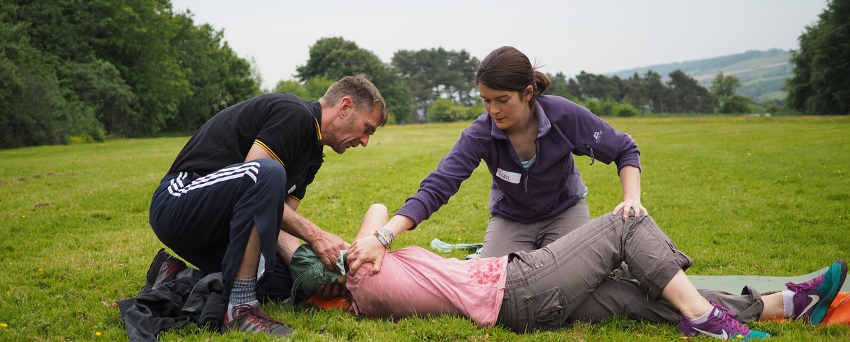 2 adults performing first aid