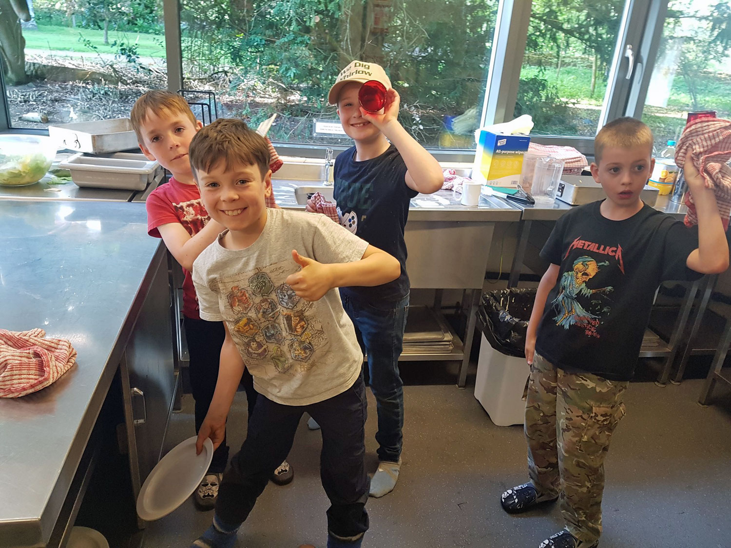School children playfully dry dishes in the kitchen