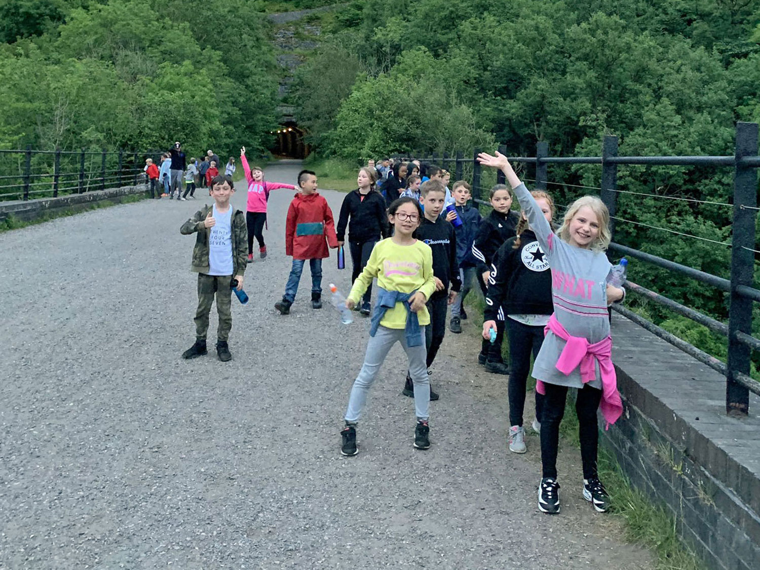 School children wave and smile for the camera as they stroll along the viaduct