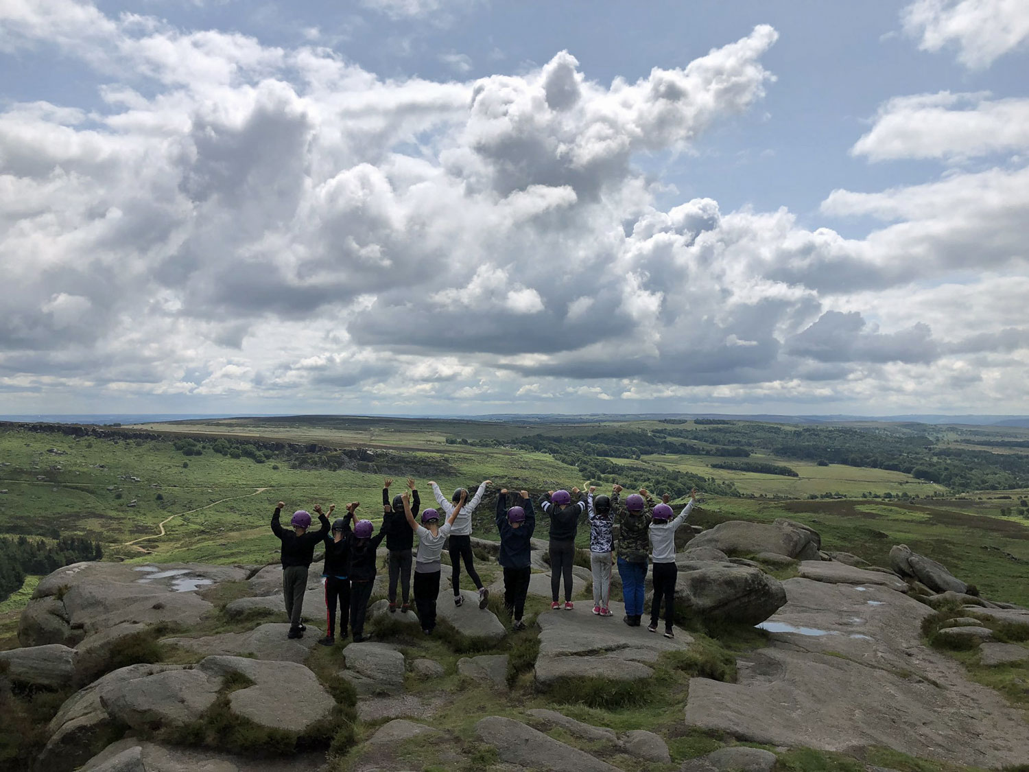School children in helmets stand on on an edge looking out over the vast Peak District scenery with their arms raised jubilantly
