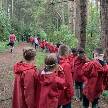 School children wearing goggles and red cagoules walk the Night Line in the woods at Thornbridge Outdoors
