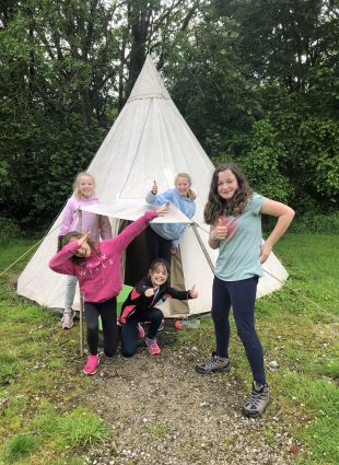 Children give the camera a thumbs up as they pose in front of their teepee