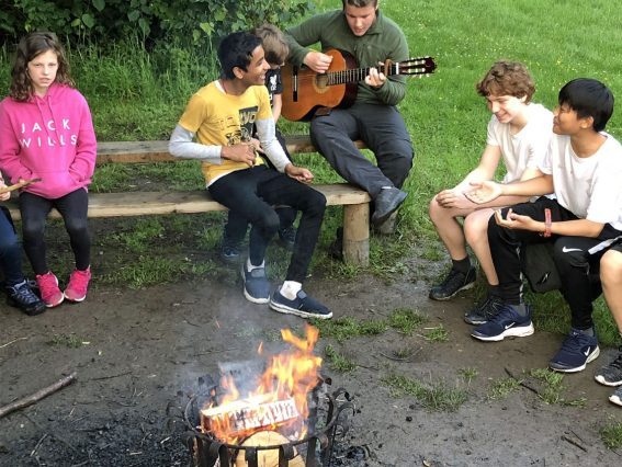 Young adults sit around the campfire one play the guitar and another sings