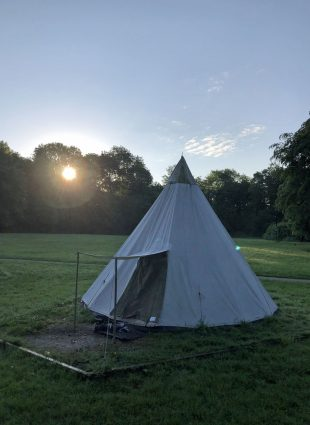 Teepee at dawn with the sun rising through the trees