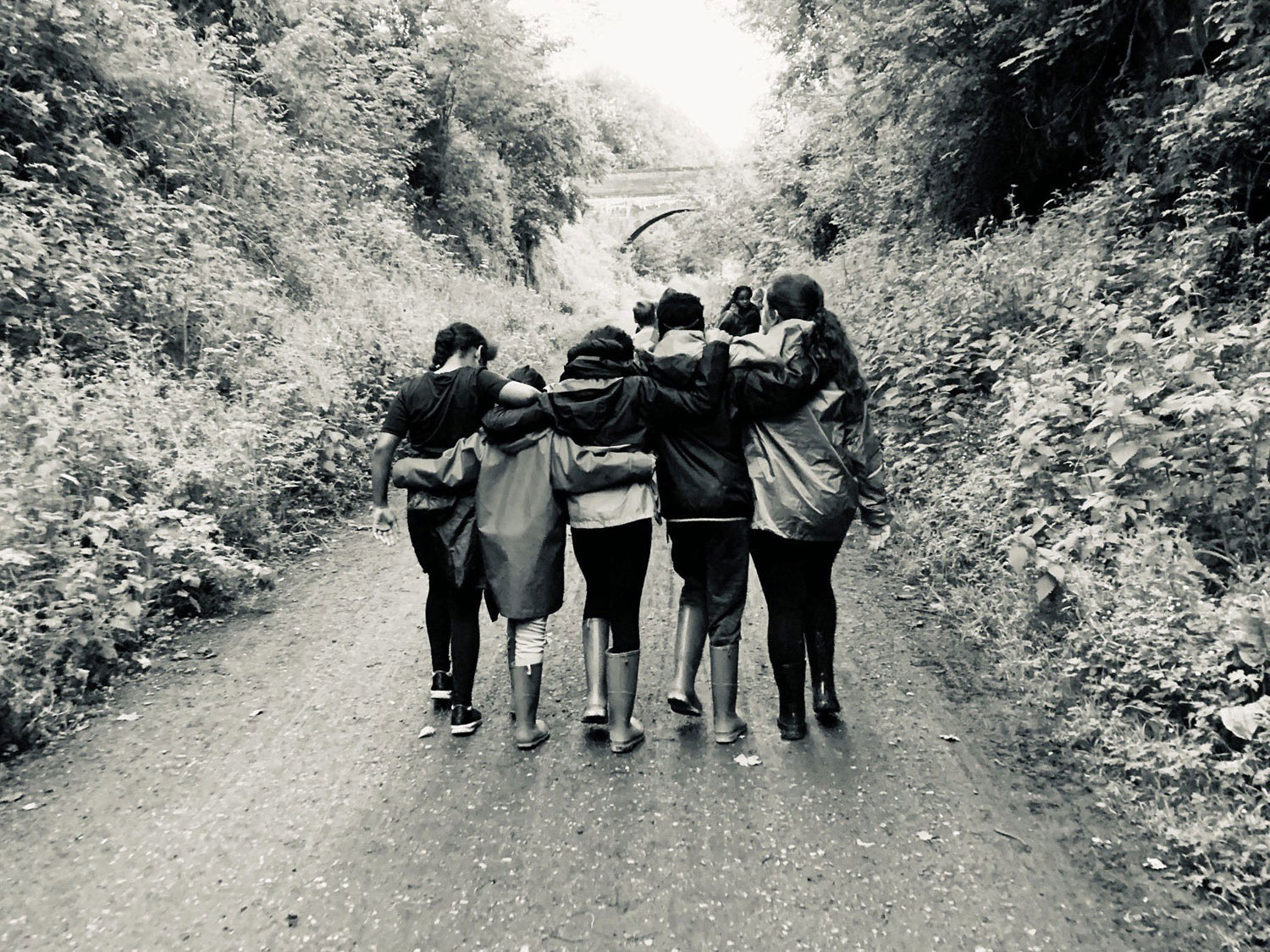 Black and white photo taken from behind shows a group of five girls walking down the Monsal Trail with their arms around eachother