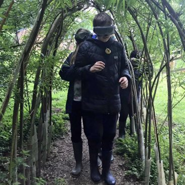Children walk beneath a willow archway with Night Line goggles on, unable to see