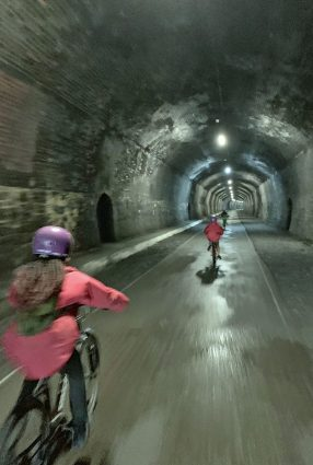 Children ride bikes in a tunnel on the Monsal Trail