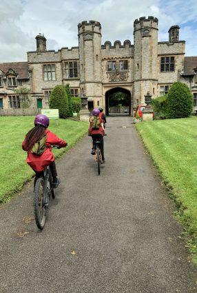 Children ride bikes up the driveway entrance to Thornbridge Outdoors