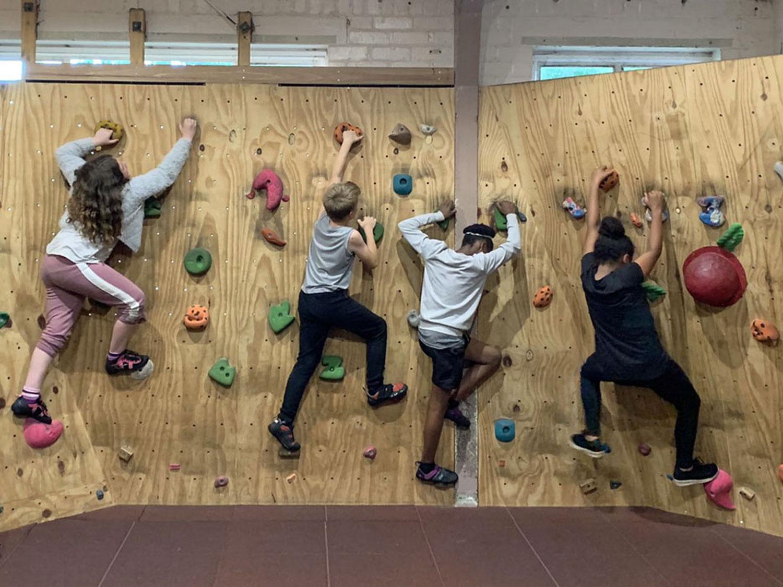 Children climb the indoor bouldering wall