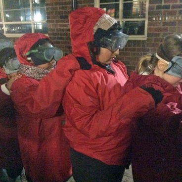 Students hold onto eachother's shoulders as they stand in a line wearing big coats and goggles for the Night Line challenge under the cover of darkness