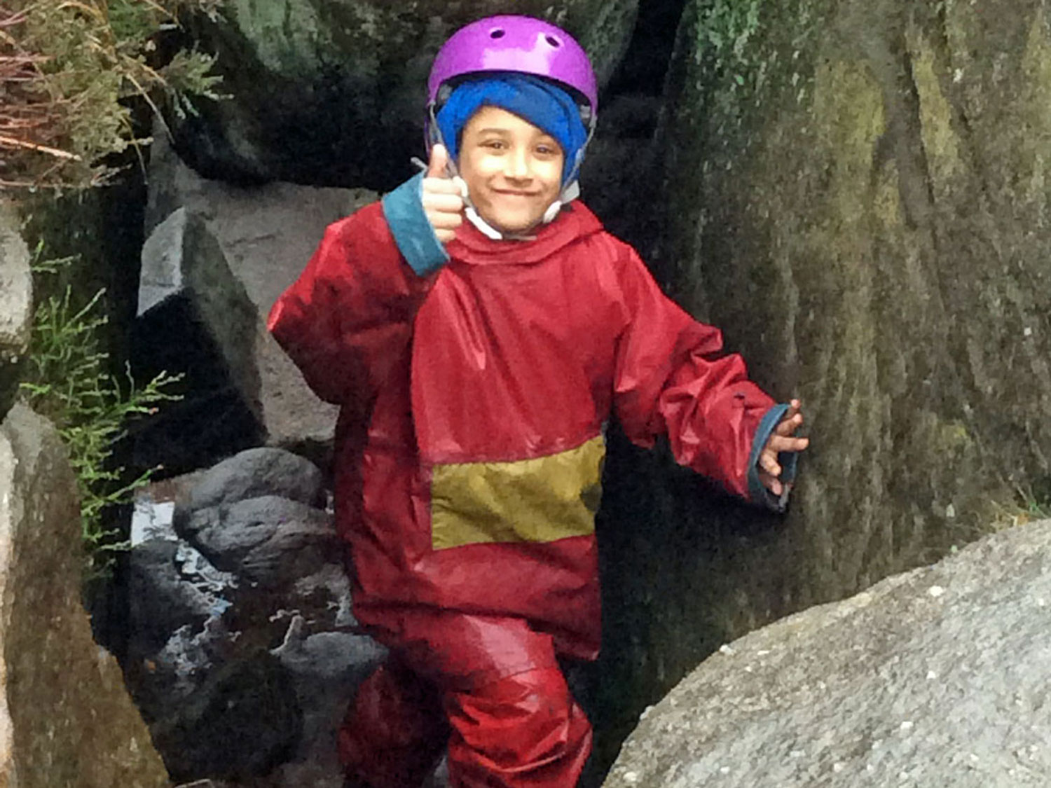 School child gives the camera and smile and a thumbs up as he clambers between boulders on a weaselling session in the Peak District