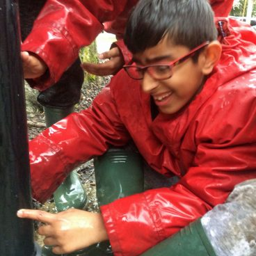 Student in a soaked cagoule grins while taking part in a team problem solving challenge