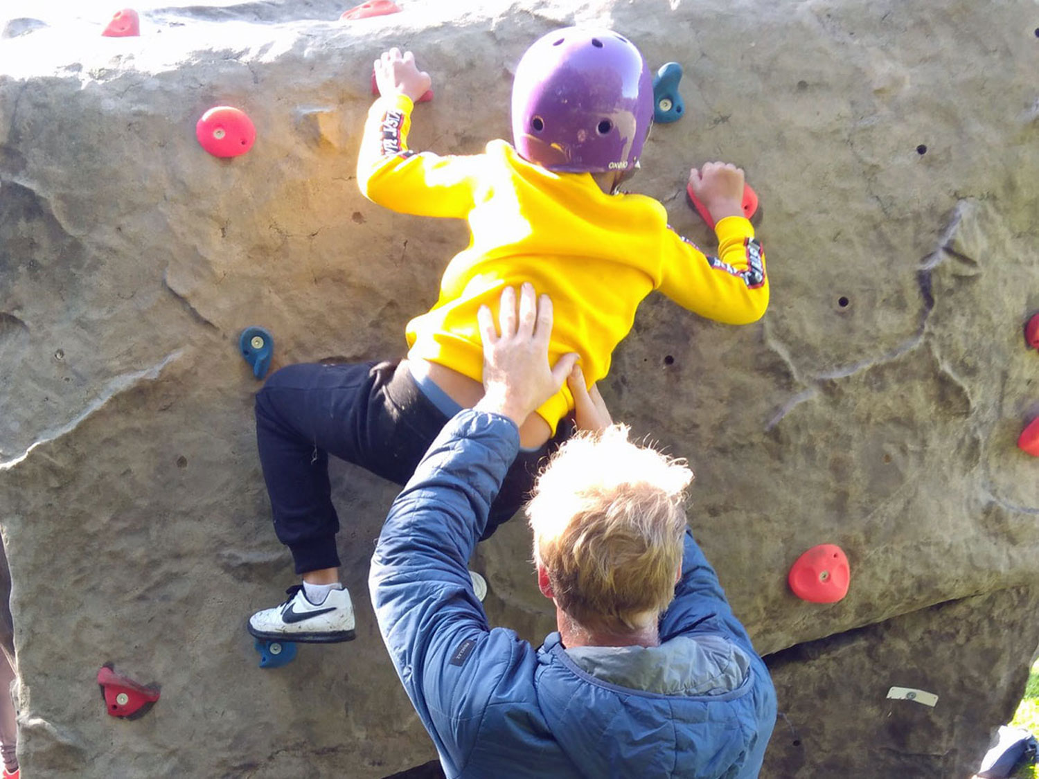 The instructor supports a small child who is climbing the outdoor boulder