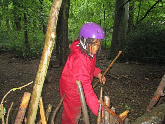 A school child builds a den from sticks in the woods