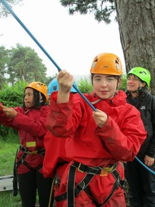 School children hold the belaying ropes and look up from the sidelines while their friends climb the cargo net