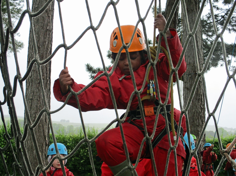Small boy climbs the cargo net