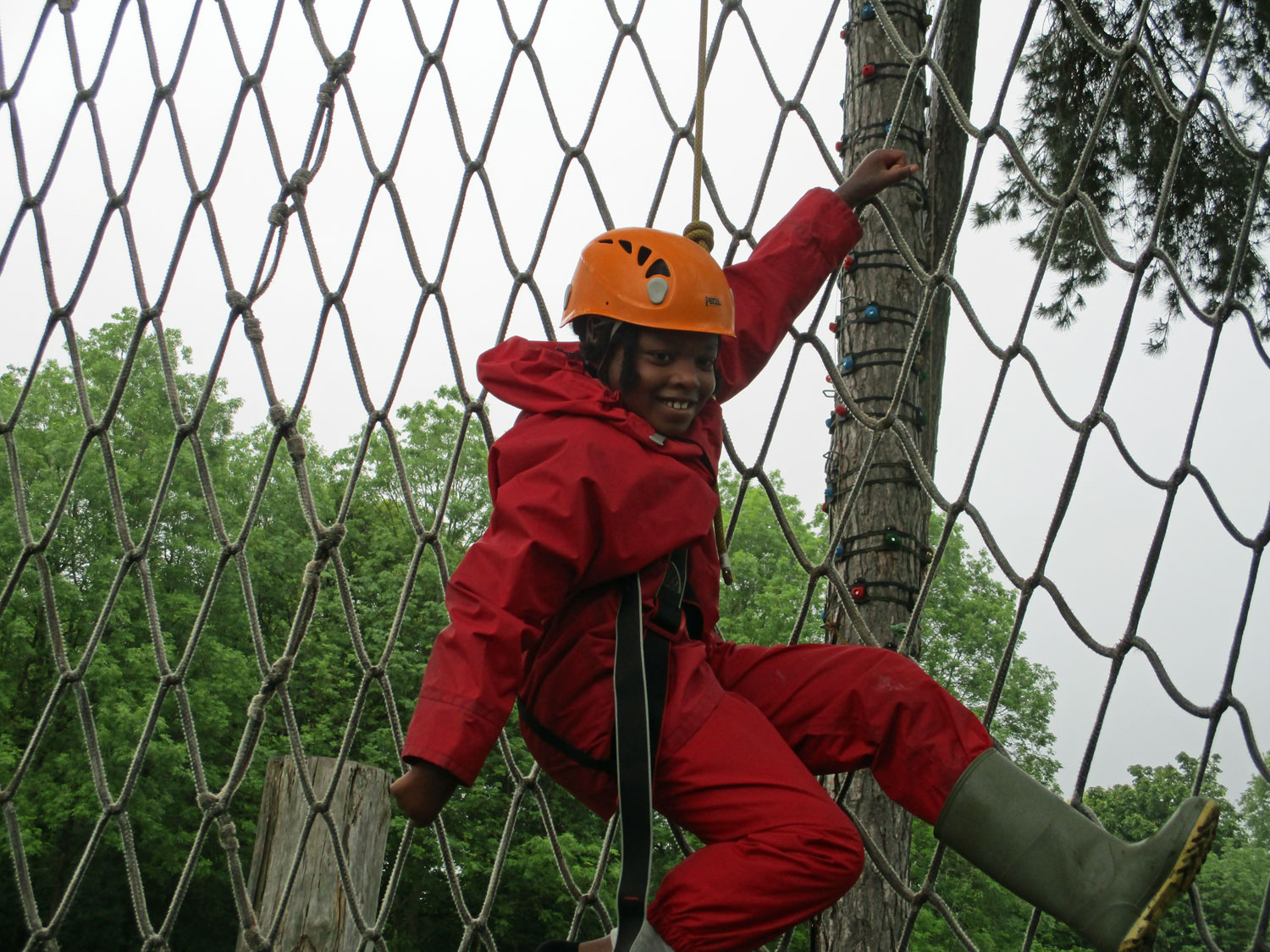 Small boy grins while dangling from his support rope after finishing his cargo net climb