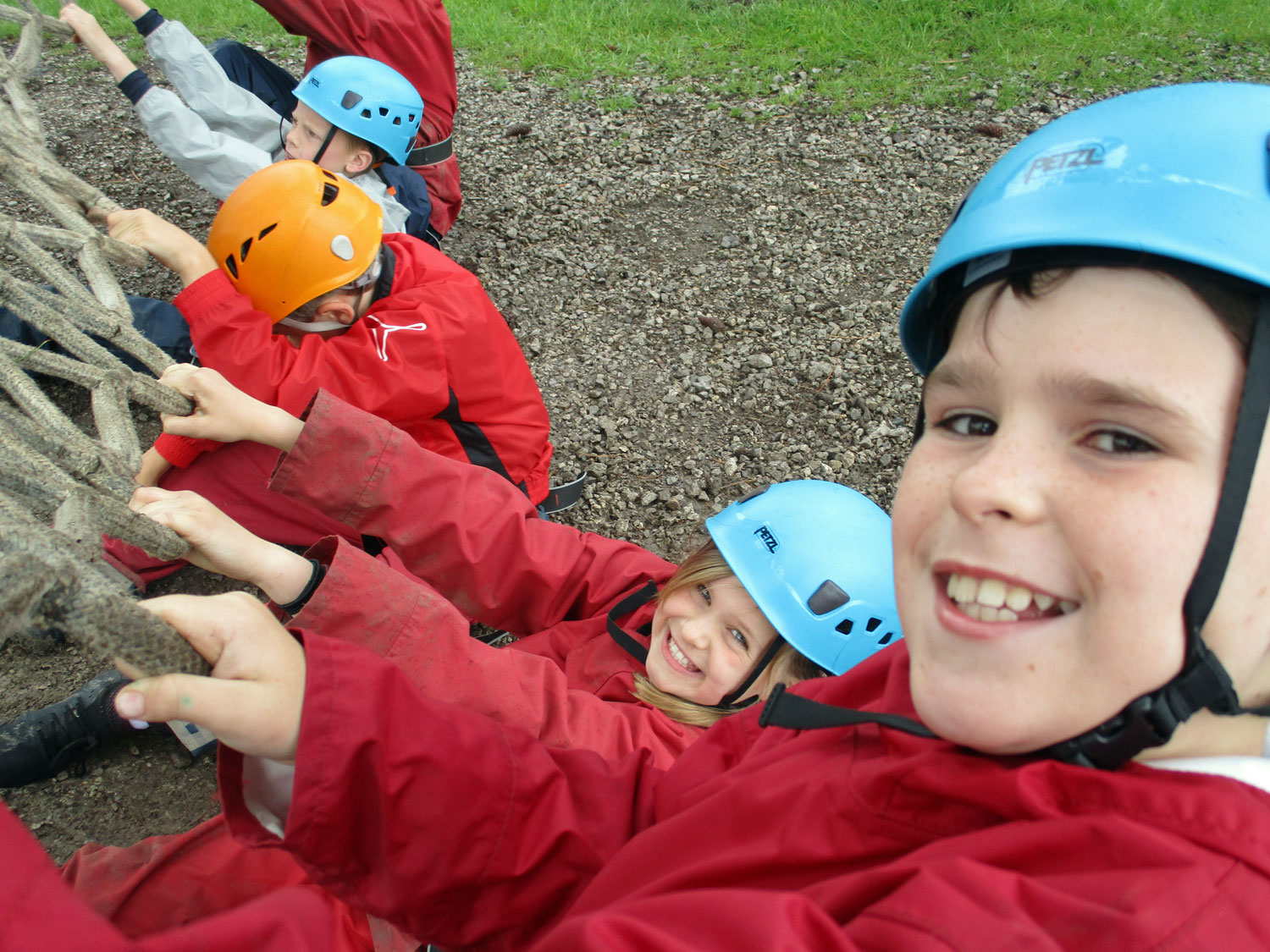 School children grin as they pull on the bottom of the cargo net to help their classmates as they climb up above