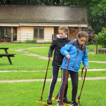 Two school girls work together to walk on two wooden planks across the field