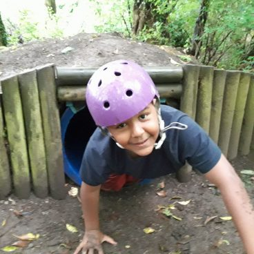 Boy crawls out of tunnel in the woods of Thornbridge Outdoors with a helmet on, he's muddy and smiling