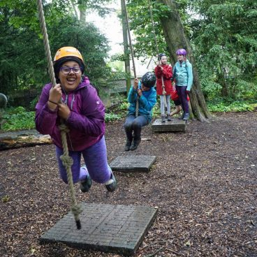 Four students swing on the low rope course in the woods