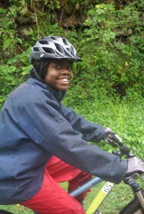 Boy smiles as he rides his bike
