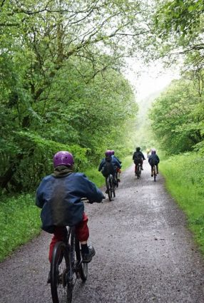 Photo taken from behind shows school children riding bikes along a green bushy stretch of the Monsal Trail