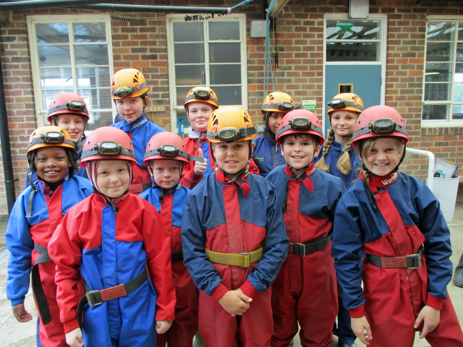 Students stand for a group photo wearing their caving suits and helmets with headtorches