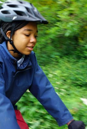 School girl rides bicycle in the grounds of Thornbridge Outdoors