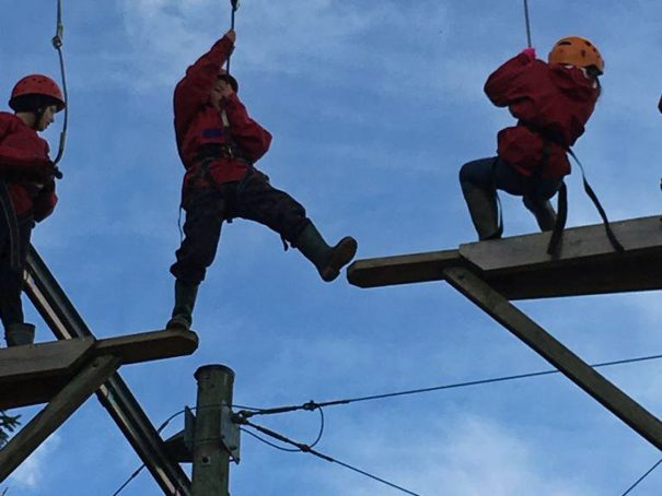 Child takes a big step across the leap of faith up the Sky Ropes