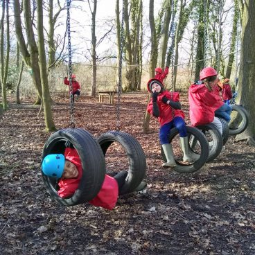 Children swing from tyres on the low rope course and smile for the camera