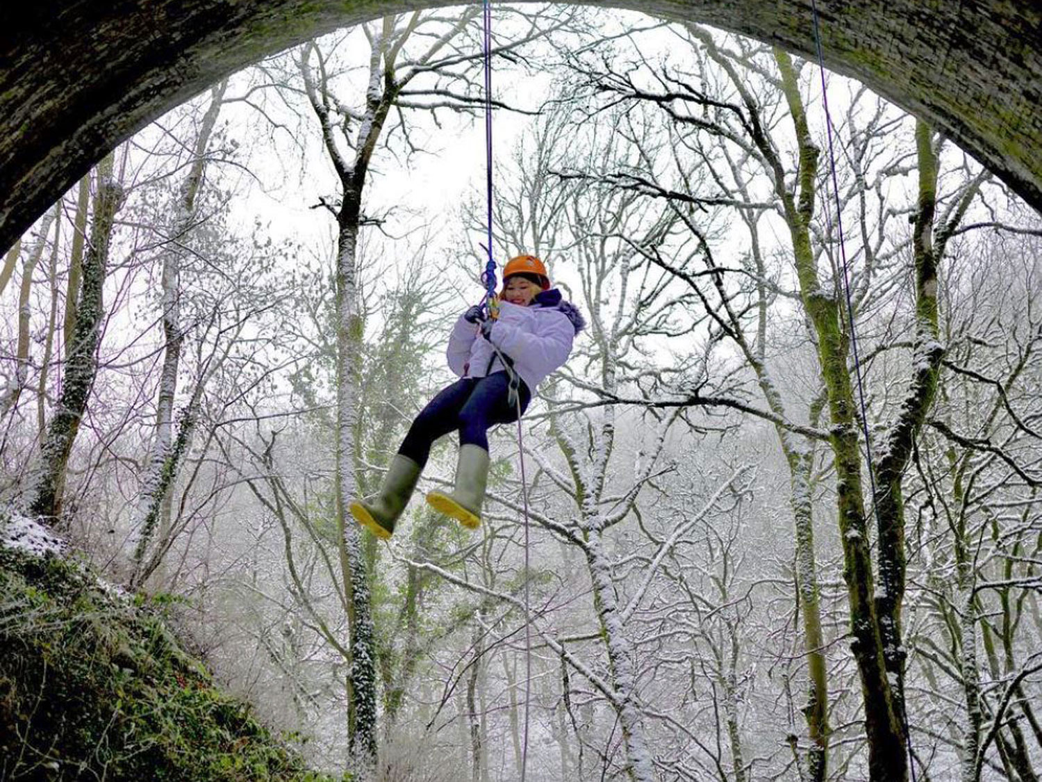 Guest abseiling from a bridge in winter