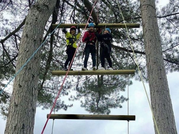 Three students stand atop the Jacob's ladder smiling as they've made it to the highest rung